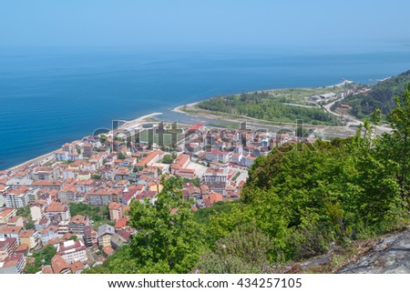 General top view of Ayancik town in Sinop in Black Sea region inside green trees with blue sea, on bright sky background.