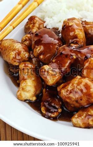General Tso's Chicken served with white rice. Shallow depth of field. - stock photo