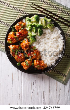 General Tso's chicken with rice, onions and broccoli on the table. vertical top view - stock photo