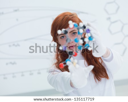 general-view  of a student in a chemistry lab looking in the camera and holding in hands and analyzing DMT molecular model and a white board on the background - stock photo