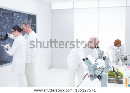 general-view of a teacher in a chemistry lab pointing formulas on a blackboard for his student taking notes while another two scientists analyzing under microscope - stock photo