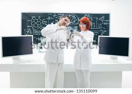 general-view of two people analyzing molecules in a chemistry lab with a worktable and a blackboard on the background - stock photo