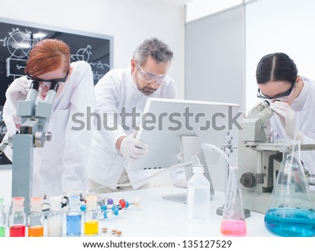 general-view of two students in a chemistry lab analyzing under microscope around lab tools and colorful liquids while the teacher is looking on a pc monitor - stock photo