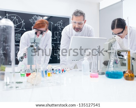 general-view of two students in a chemistry lab analyzing under microscope under supervision of a teacher - stock photo