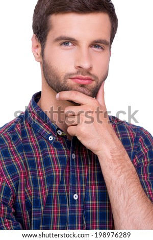Generating fresh ideas. Portrait of thoughtful young man in casual shirt holding hand on chin and looking at camera while standing isolated on white - stock photo