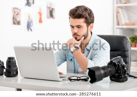 Generating new ideas. Concentrated young man holding hand on chin and looking at laptop while sitting at his working place - stock photo