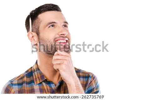 Generating new ideas. Thoughtful young male carpenter holding hand on chin and looking away with smile while standing against white background  - stock photo