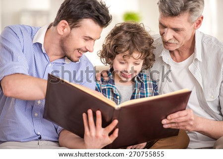 Generation portrait. Grandfather, father and son sitting and reading a book on sofa. - stock photo