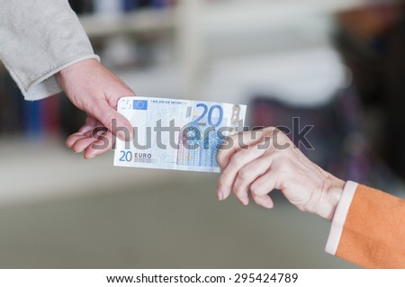 Generational conflict, old woman and young woman pulling on a euro banknote. - stock photo