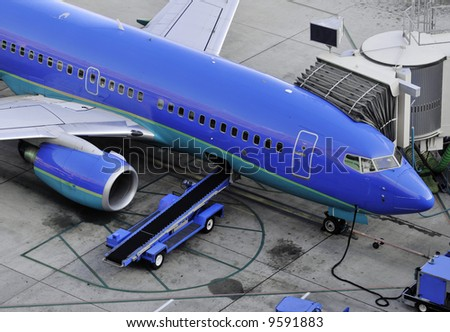 Generic aircraft parked next to a jetty. loading with passengers at airport terminal. - stock photo
