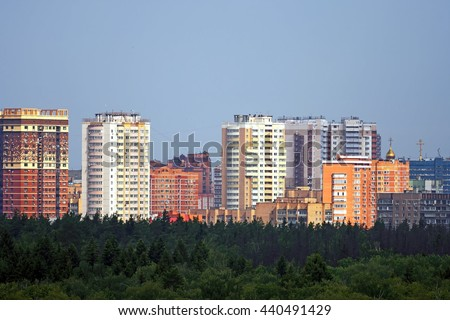 generic city landmark with various residential towers and old residential buildings forest on foreground close up view
