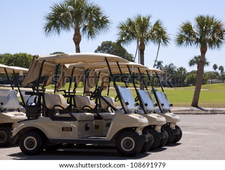 Generic club car golf carts in a parking lot in Florida. - stock photo