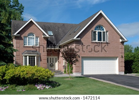 Generic contemporary upscale suburban brick house and manicured lawn