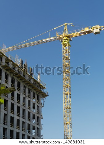 Generic highrise building under construction and jib crane over clear blue sky - stock photo
