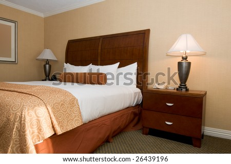 Generic hotel/motel room with queen-size bed, patterned blanket and carpet (note: framed painting on the wall has been blurred/defocused on purpose)