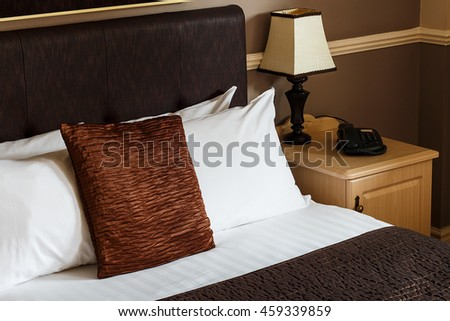Generic hotel room example with freshly made bed, clean sheets and a plain neutral decor which can be found in any motel bedroom or bed and breakfast accommodation.