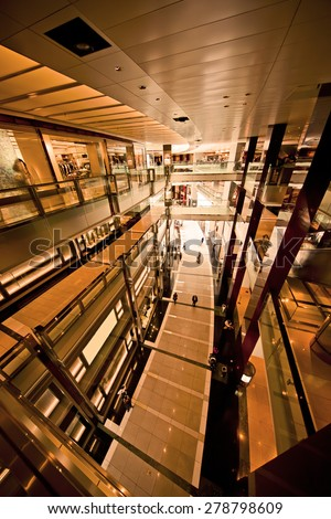 Generic interior of a modern shopping center with orange filter - stock photo