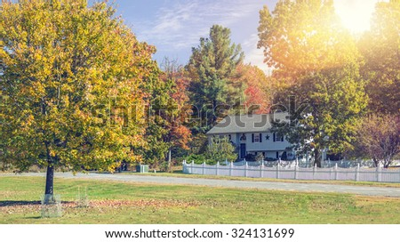 Generic looking New England traditional house in the fall - stock photo