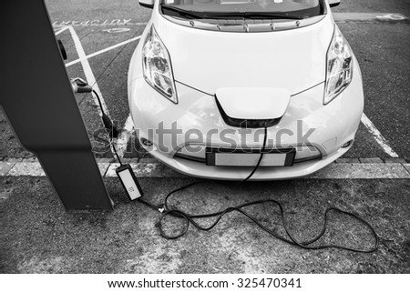 Generic modern electric car plugged into electricity recharging system station black and white image - stock photo