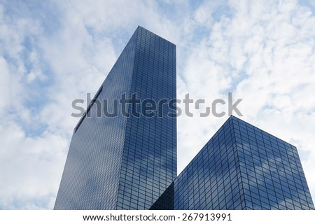 generic office building skyscraper with glass facade reflecting sky and clouds - stock photo