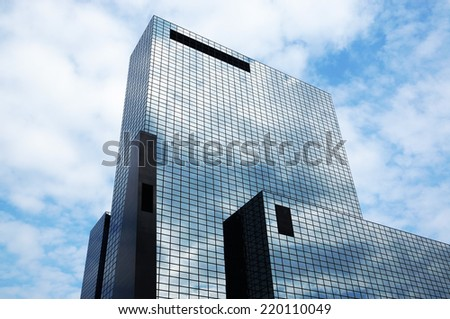 generic office building with glass facade reflecting sky and clouds - stock photo