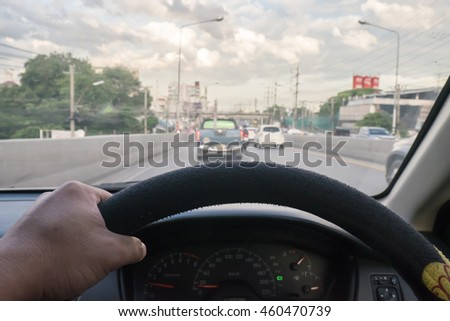 Generic photo of man driving a car through slight turn.