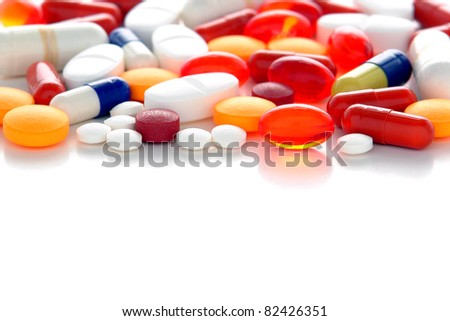 Generic prescription medicine drugs pills and assorted pharmaceutical tablets with gel caps of assorted colors and shapes over white
