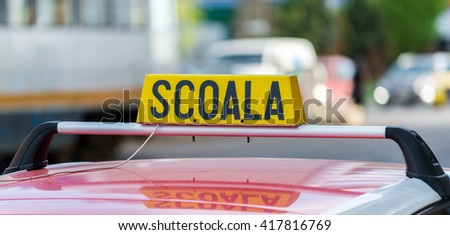 Generic Romanian driving school car sign on street background. School word in romanian language.