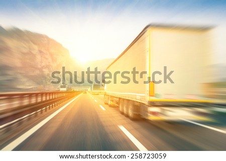 Generic semi trucks speeding on the highway at sunset - Transport industry concept with semitruck containers driving to the mountain pass - Warm editing with pop filtered sunshine and blurred edges - stock photo