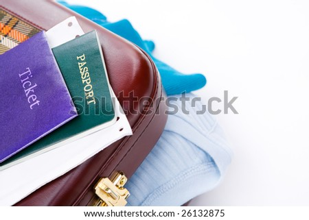Generic ticket, passport and boarding pass on travel suitcase with some shirt shown from it. - stock photo