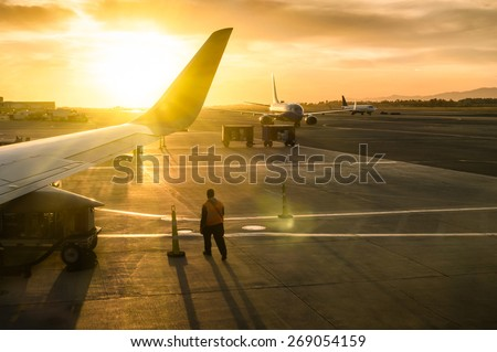 Generic working man walking near airplane wing at terminal gate of international airport at sunset - Concept of emotional travel around the world - Soft focus and sun lens flare due to backlighting - stock photo