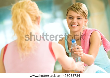 Generous girl giving bottle of water to the friend in front of her - stock photo