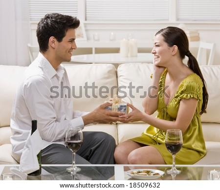 Generous man surprising wife with elegant gift on anniversary - stock photo