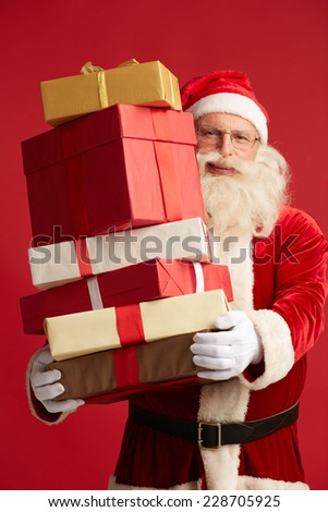 Generous Santa with pile of giftboxes looking at camera - stock photo