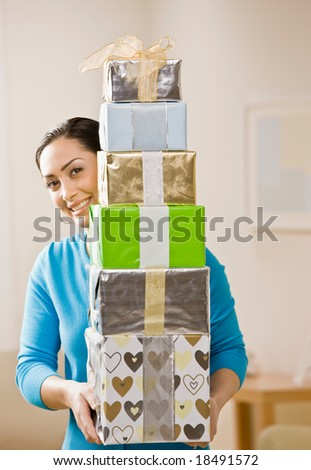 Generous woman carrying stack of festive birthday gifts - stock photo