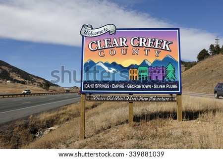 Genesee, CO, USA - November 8, 2014: Westbound on I-70 towards Idaho Springs, Empire, Georgetown, Silver Plume and more towns, Where Old West Meets New Adventure, sign.  - stock photo