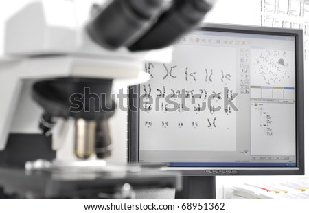 Genetic investigation with microscope and computer - stock photo