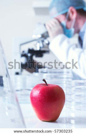 Genetically modified red apple and scientist selective focus - stock photo