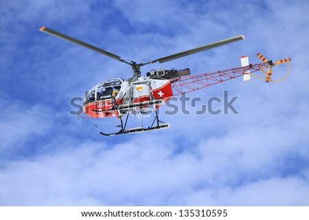 GENEVA - MARCH 10 : Air-glaciers helicopter flying in cloudy sky upon swiss Alp mountains - Geneva on March 10, 2013 in Geneva, Switzerland. - stock photo
