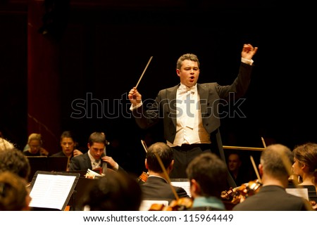 GENEVA - MARCH 16: Conductor Antoine Marguier conducts the United Nations Orchestra at the Victoria Hall March 16, 2012 in Geneva, Switzerland. - stock photo
