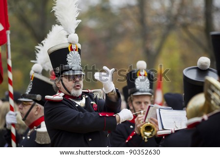 GENEVA - NOVEMBER 13: Bandmaster conducts the military band at the memorial service to Geneva soldiers on November 13, 2011 in Geneva Switzerland, attended by veterans and serving soldiers - stock photo