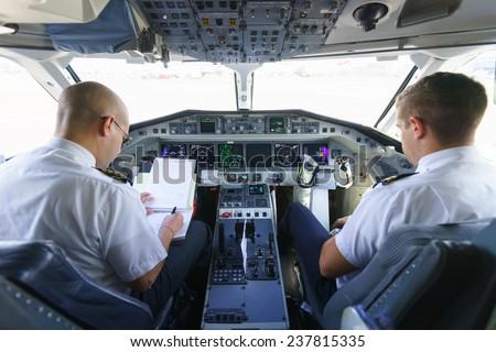 GENEVA - SEPTEMBER 16: Etihad Regional pilots in aircraft cockpit on September 16, 2014 in Geneva, Switzerland. Darwin Airline, operating under the brand name Etihad Regional since January 2014 - stock photo