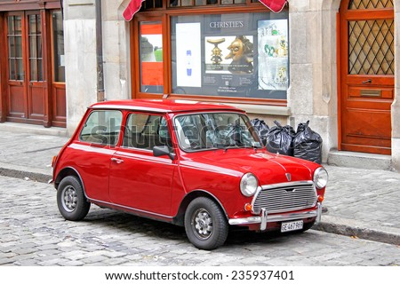 GENEVA, SWITZERLAND - AUGUST 4, 2014: Red classical car Austin Mini Cooper at the city street. - stock photo