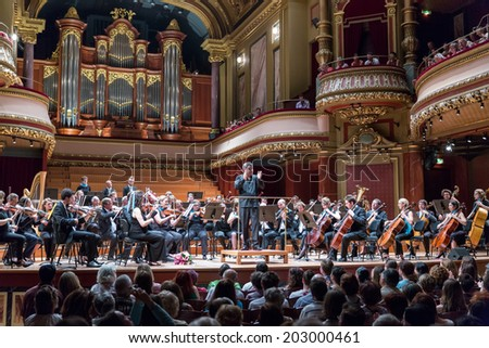 GENEVA, SWITZERLAND - JUNE 22, 2014: Antoine Marguier conducts the United Nations Orchestra and the audience at the Victoria Hall during a free concert as part of the city's festival of music. - stock photo