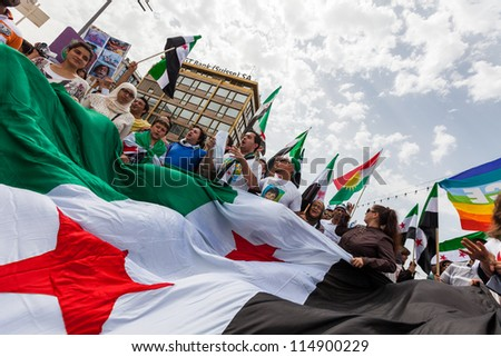 GENEVA, SWITZERLAND - JUNE 30: Unidentified protesters during a protest against President of Syria Bashar al Asaad in the center of the city of Geneva, June 30, 2012 in Geneva, Switzerland. - stock photo