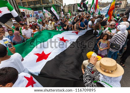 GENEVA, SWITZERLAND - JUNE 30: Unidentified protesters holding the syrian flag during a protest against President of Syria Bashar al Asaad in the city of Geneva, June 30, 2012 in Geneva, Switzerland. - stock photo