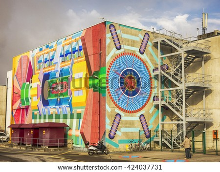 GENEVA, SWITZERLAND - NOV 24, 2014: The exterior of the Atlas lab building at CERN in Geneva shows a picture of the physics of the large hadron collider inside. - stock photo