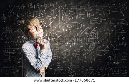 Genius boy in red glasses near blackboard with formulas - stock photo