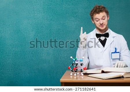 Genius. Funny young professor in white coat with microscope and books pointing up - stock photo