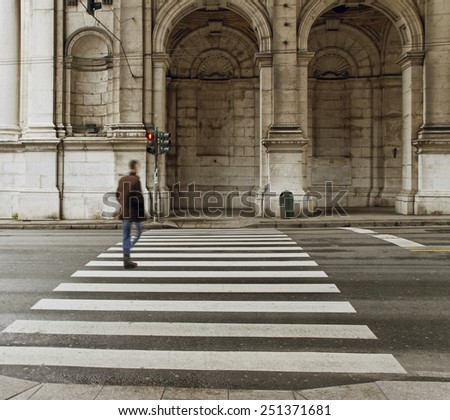 GENOA, ITALY - APRIL 6: Man crossing a street Via Settembre. It is street of the historical centre of Genoa on April 06, 2013. - stock photo
